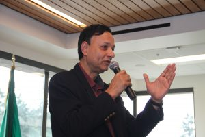 Singh, speaking with a microphone.