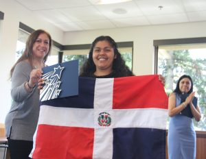 Grad holding folder and Dominican Republic flag