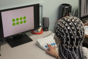 A student wears a netting of white circles and cords on her head while sitting at a computer. Her hand rests on a button.
