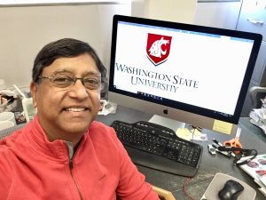 Portrait of Pappu in his office, with a WSU logo on the computer screen behind him.