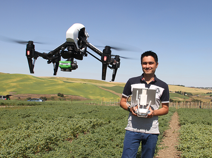 Valencia, standing with controls in a field, as a drone flies near him.