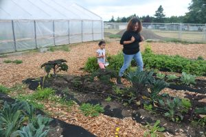 A woman and child walk in a garden with greenhouse in the background.