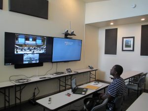 A student sits at a desk looking at 2 big monitors on the wall. 1 monitor shows a classroom in another city.