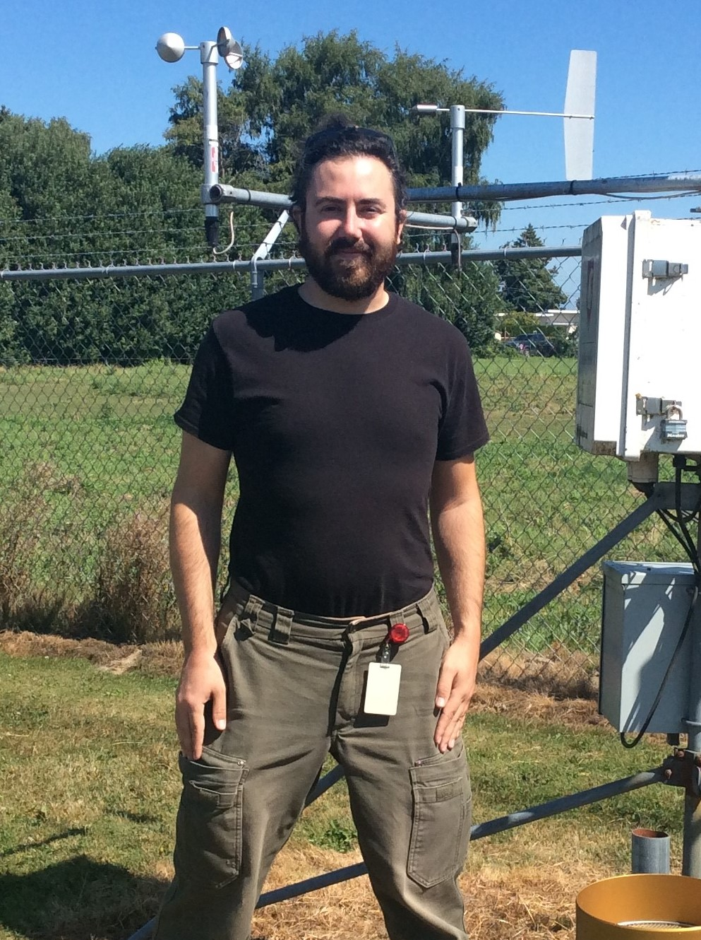 Contezac poses in front of a weather station, that includes a wind speed indicator and other electronic equipment.