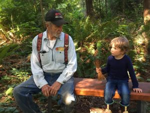 Family members sit on log at Forestry field day.