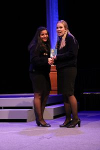 Arroyo-Mejia stands on a stage in an FFA jacket holding a plaque with another woman.