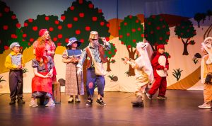 Youth in costume act on stage in a production of Johnny Appleseed.
