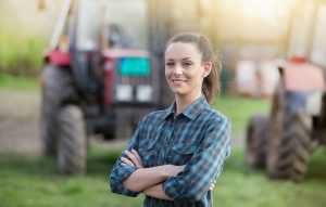 Woman farmer standing on farmland with crossed arms and tractors in background