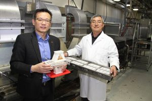 Scientists hold a plastic model of the microwave process, and a tray of packaged meals, in front of a large machine.