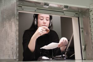 Woman with headphones in tasting lab holds chocolate.