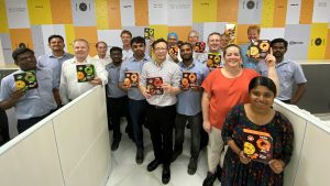 Group photo in an open office, with employees holding brightly colored packaged food boxes.