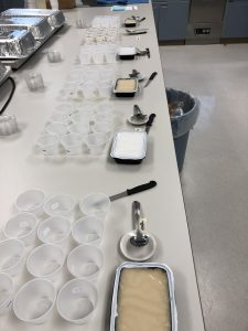 Multiple plastic trays with mashed potatoes in them on a table. Each tray is surrounded by several small, empty numbered plastic cups that are used to provide samples to tasters.