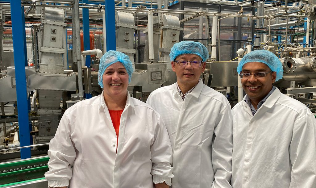Group of three in lab coats and sanitary caps with food machinery in background.