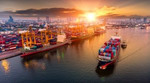 Busy port with cargo ship sailing near cranes, freight