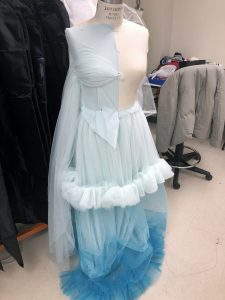 A blue and white dress with ombre fading and wispy white ruffles.