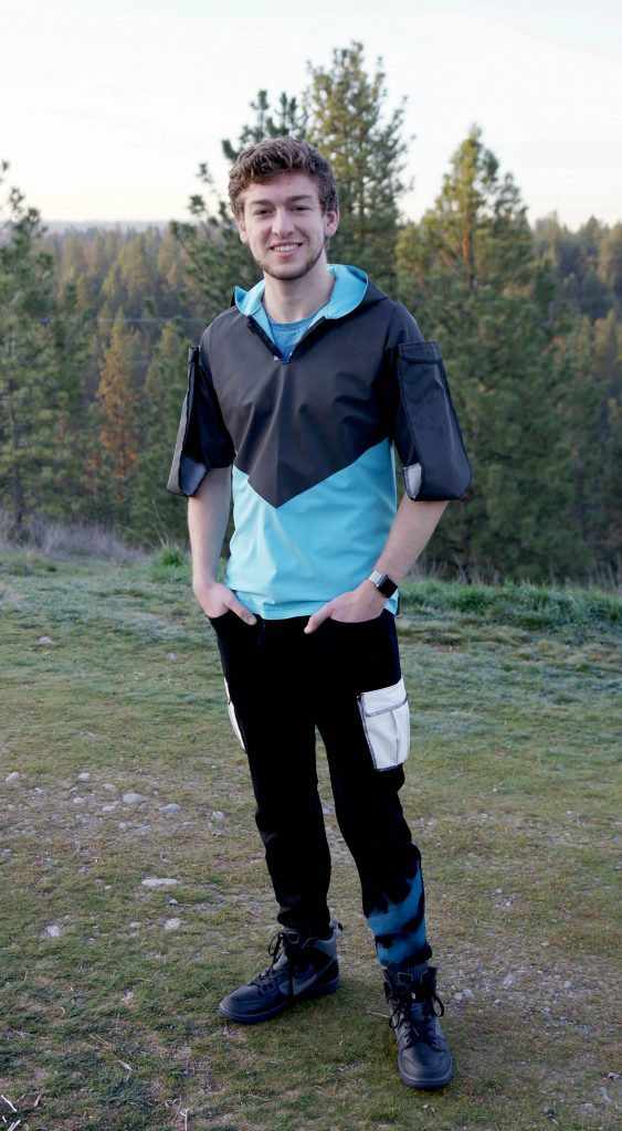Young man wearing bright blue and black jacket standing on a grass field.