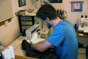 A young man in a blue shirt working on a sewing machine.