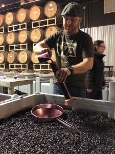 West stands behind a large vat full of grapes, holding a long cylinder in one hand and pours grape juice into it with the other.