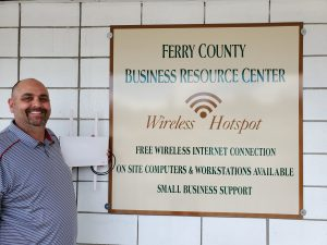 Lane, left, stands with router next to sign reading Ferry County Business Resource Center Wireless Hotspot.