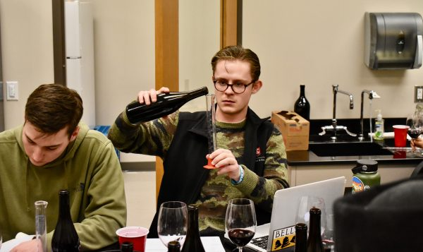 Gerow pours wine from a bottle into a large glass test tube.