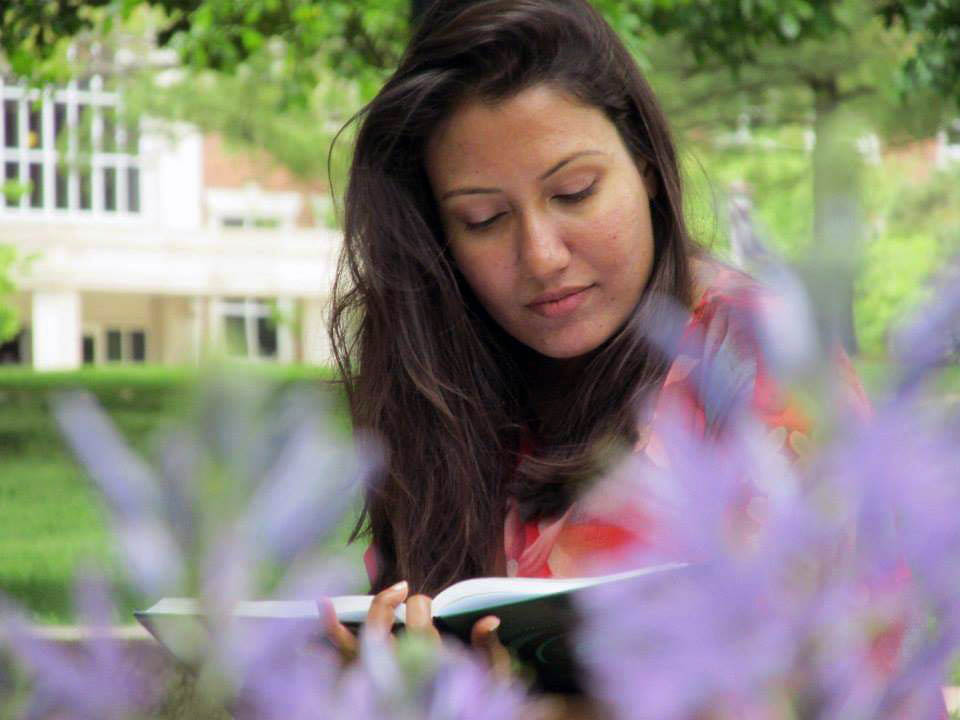A young woman reading a book next to flowers on a campus lawn.