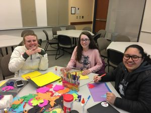 Three female students coloring at a large table.