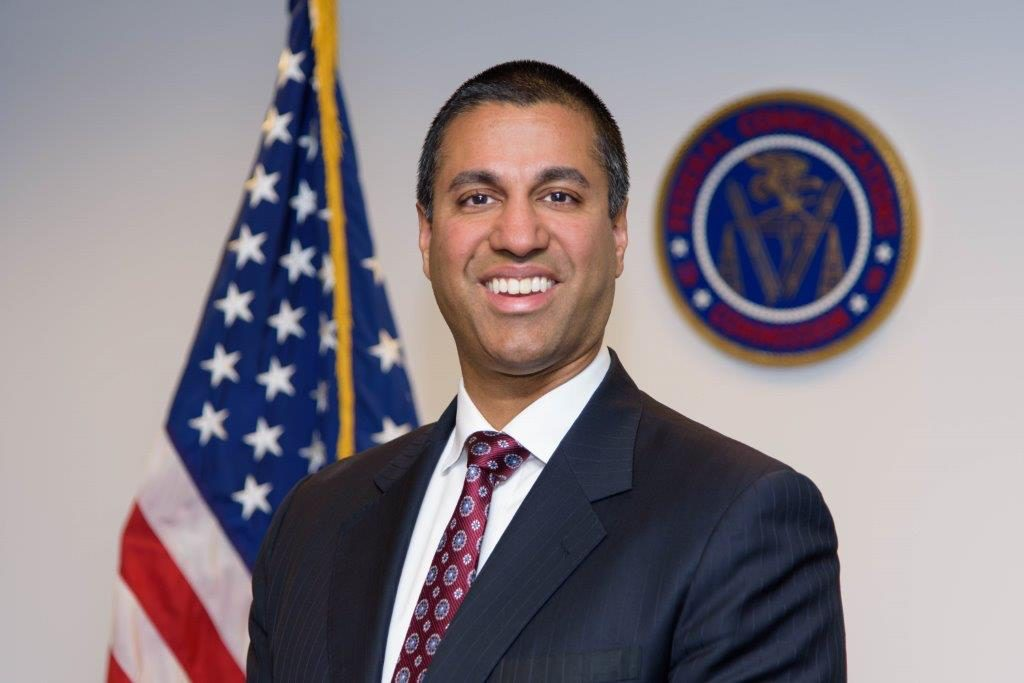 Portrait of Ajit Pai with US Flag, official seal on wall