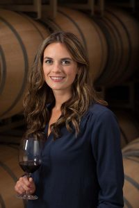 A woman with curly brown hair stands in front of a barrel with a glass of red wine.