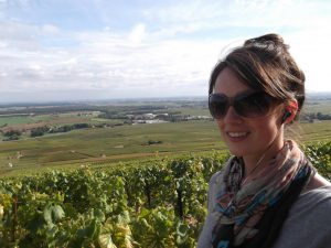 A woman with brown hair smiles in front of a large green vineyard in France.