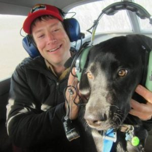 Peterson, with headset in aircraft, with a dog, also wearing a headset.
