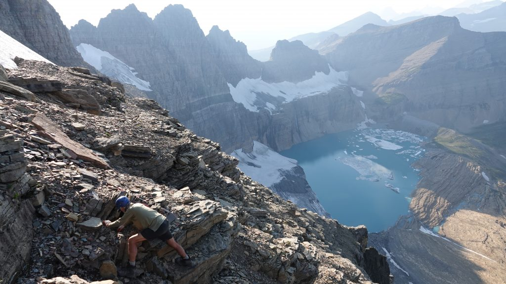 A technician examining rocks in the foreground, overlooking a glacial basin in the background.