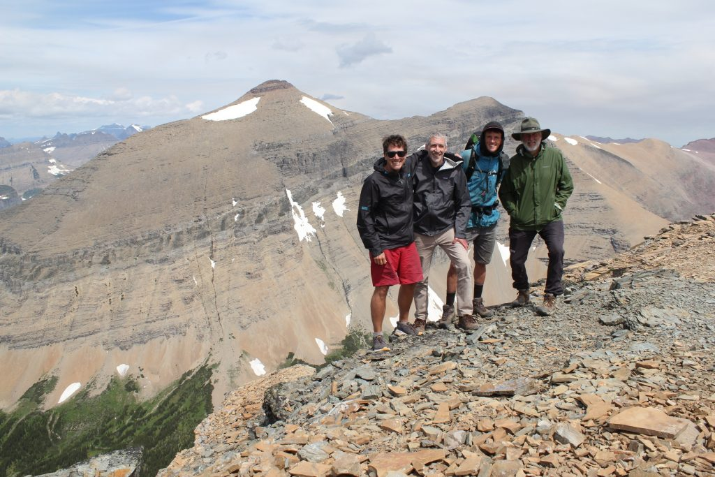 Group of scientists standing on a slope overlooking mountains.
