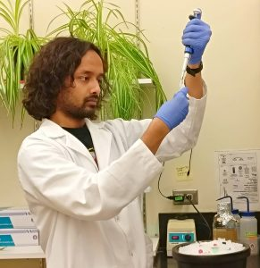 A young man wears a lab coat and gloves and he conducts a science experiment.