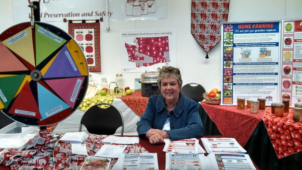 A woman sits at a booth surrounded by colorful posters about food preservation.