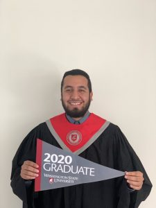 "Garcia holds a pennant saying ""2020 Graduate"" while wearing formal graduation robes."