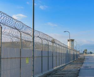 Chain link fence with multiple rolls of barbed wire along the top. A guard tower is seen in the distance.
