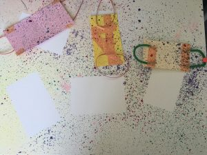 Colorful splatters of paint on a white background. Three face masks are also on the paper covered with paint. They've been moved from their original location, showing off paint-free white areas on the paper.