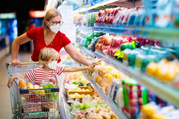 A mother and her young son select items from a stack of fruit in a supermarket while wearing masks.