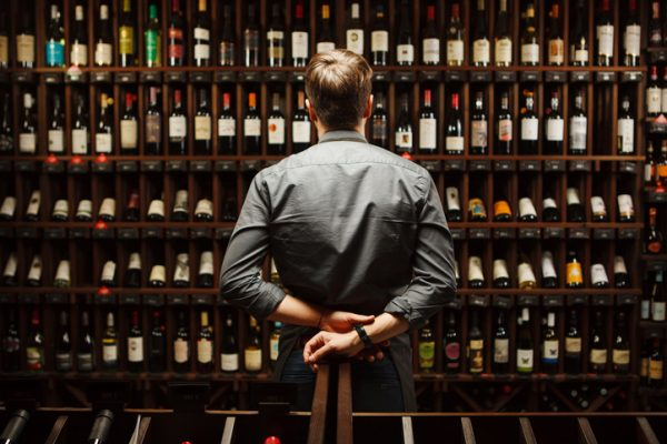 A man in a grey shirt stands facing a wall of wine bottles.