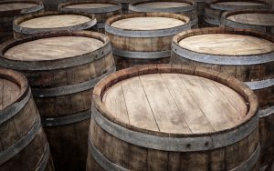Wood wine barrels are packed together in a wine cellar.