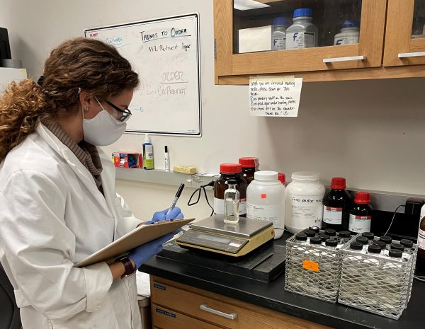A woman with a clipboard in a lab coat monitors equipment.