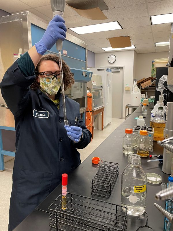A woman in a lab coat and gloves holds samples of saccharomyces yeast.