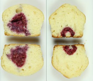 2 muffins cut vertically in half. On the left, there's a large red splotch and no visible fruit. On the right is a small raspberry that's been cut in half in the middle of the muffin.