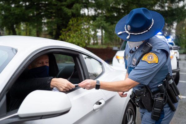 A Washington State Trooper in uniform takes a license from a man in a white sedan.