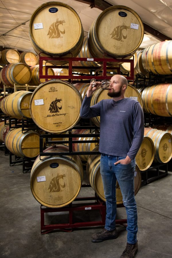 """A man in his late 20s in jeans and a grey sweatshirt samples a red wine blend while standing near a stack of wine barrels labeled """"WSU's Blended Learning."""""""