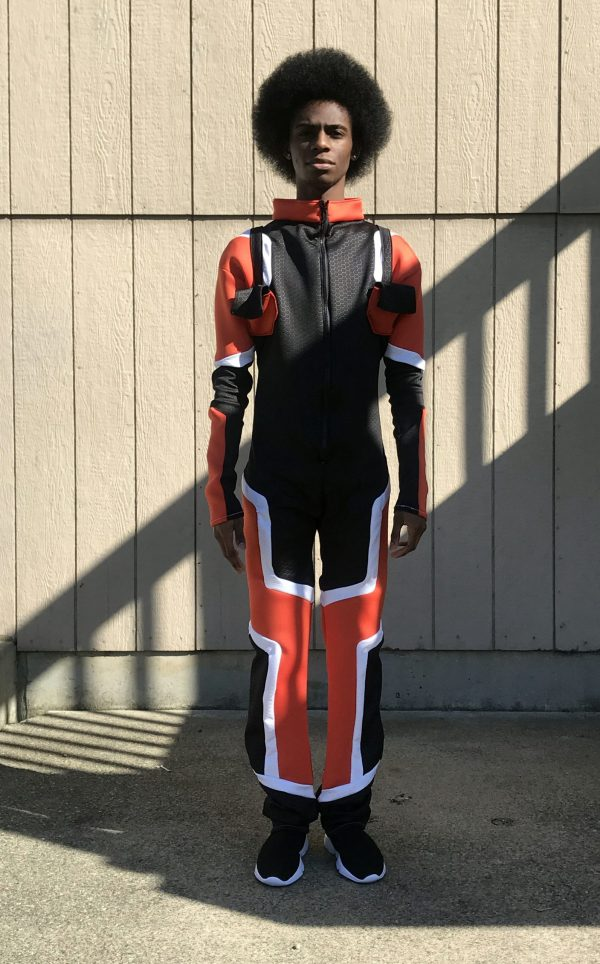 A young Black man with an afro sports a one piece black, orange and white concept suit for mars.