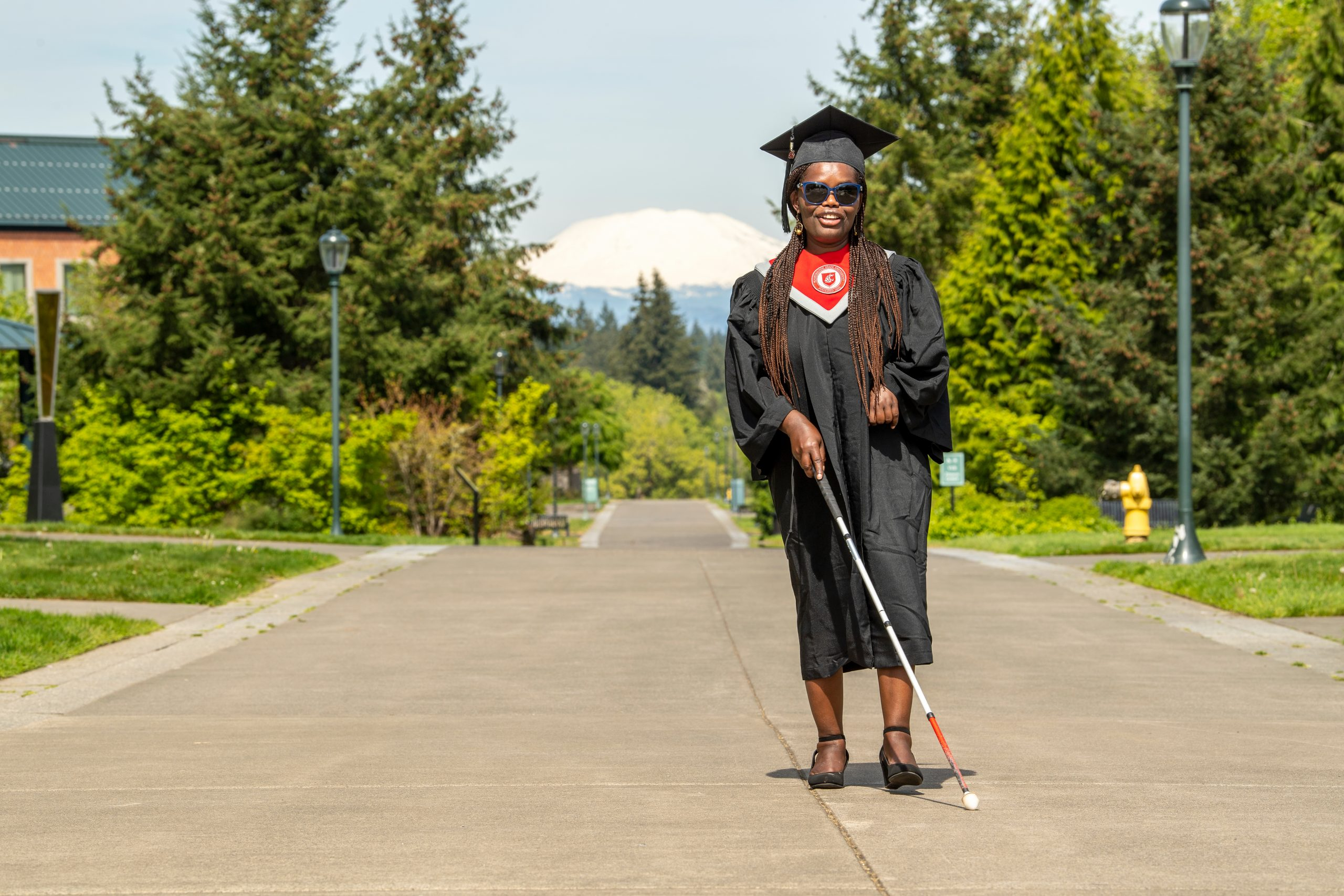 Griffith wears a WSU gap and gown walking down a sidewalk on the WSU Vancouver campus using a cane to assist.
