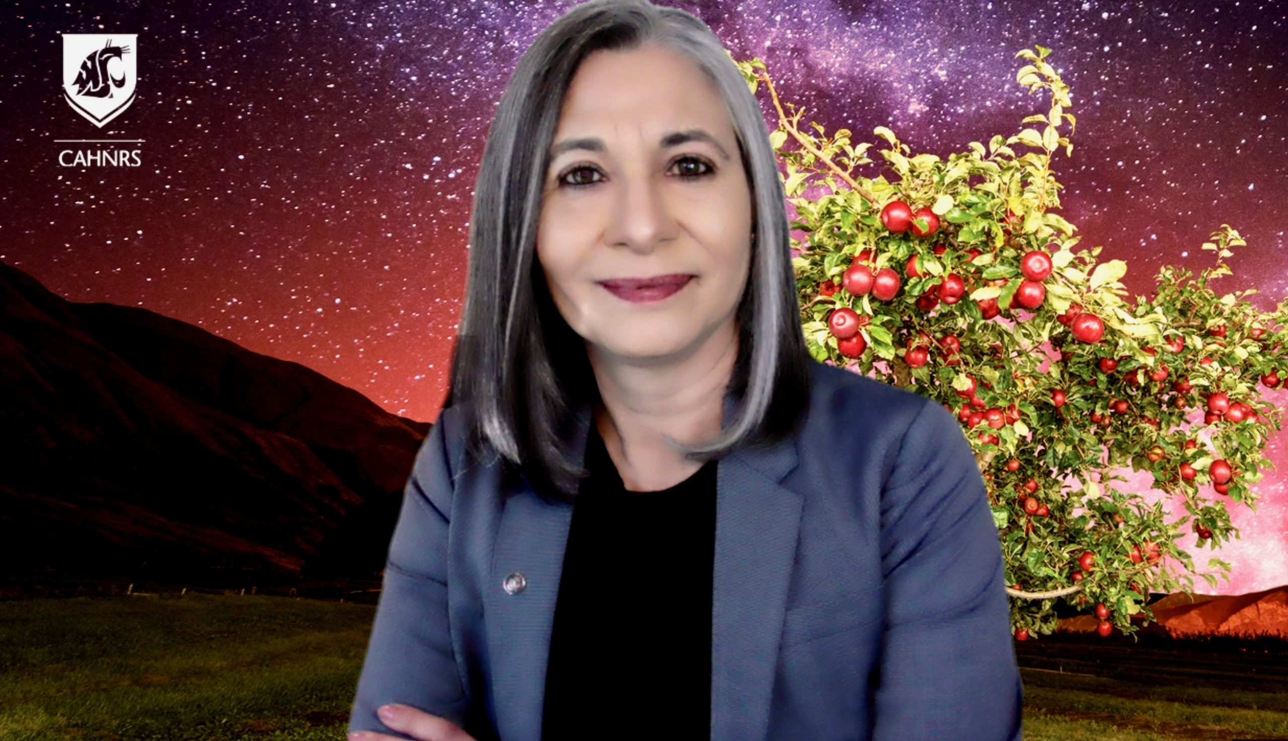 Gordillo poses in front of a stock background featuring a Cosmic Crisp apple tree