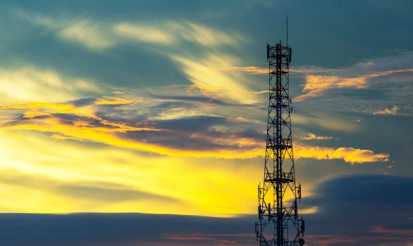 A broadband tower is pictured against a yellow sunset sky.