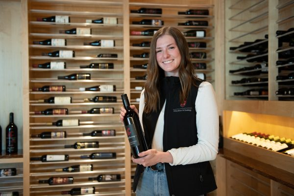 A young brunette woman in a black vest poses in front of a rack of wine with a bottle of wine.